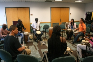 Moustapha instructing students in sabar drumming.