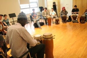 Moustapha teaching drums to students at the Cambridge School of Weston.